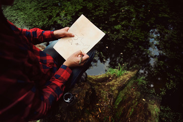 Adventurer in red checkered shirt drawing a map in search of a lost treasure. Pirates love story date. Man making the map older.