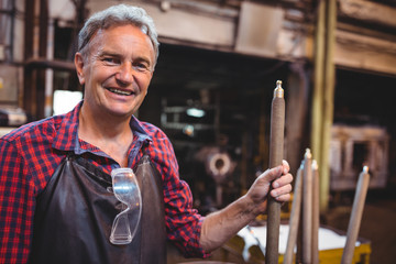 Portrait of glassblower holding blowpipe