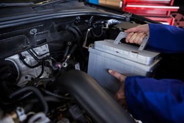 Mechanic removing car battery from car