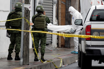 A soldier takes pictures of forensic technicians removing a body from a crime scene after unknown assailants gunned down a couple inside a restaurant in Monterrey