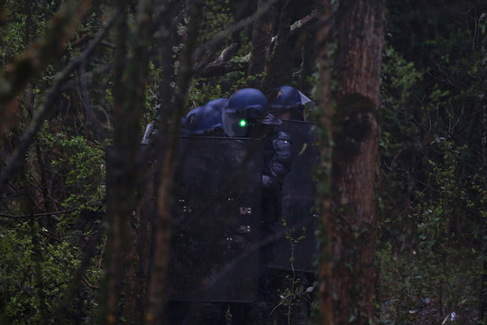 A protester flashes a laser pointer at French gendarmes during clashes with French gendarmes during an evacuation operation in the zoned ZAD (Deferred Development Zone) in Notre-Dame-des-Landes