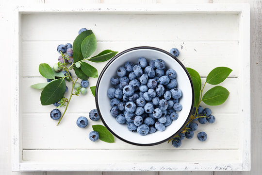Fresh ripe blueberries with leaves in bowl in white wooden tray