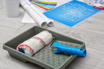 Roller brush in paint tray for interior decorating on floor