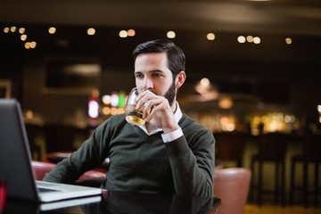 Man looking at laptop while having glass of drink