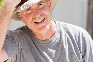 Senior male puts on his cowboy hat on hot sunny day