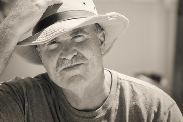Older man takes off hat in bright sun black and white vintage photo