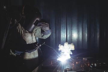 Female welder working on a piece of metal