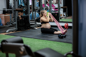 Pregnant woman exercising with resistance band