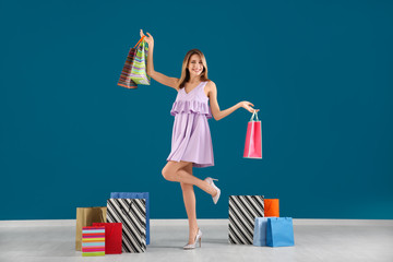 Happy young woman with shopping bags against color wall