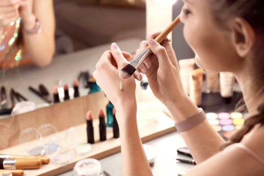 Young woman applying foundation on her hand in makeup room, closeup