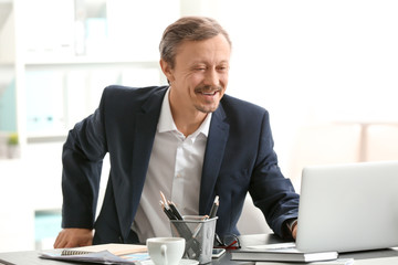 Handsome man working with laptop indoors
