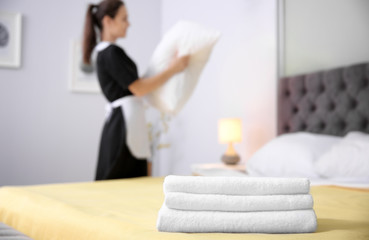 Stack of towels and blurred maid on background in hotel room