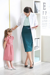 Little girl measuring her height at doctor's office