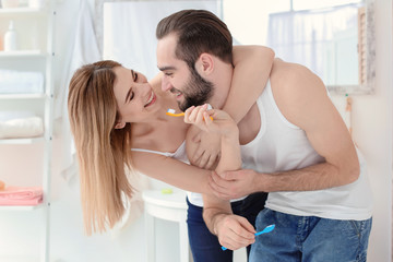 Young couple brushing teeth together in bathroom