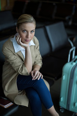 Portrait of woman sitting on chair in waiting area