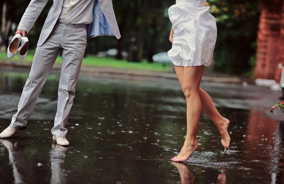 Wedding couple dancing in the rain. Close up dynamic shot in motion. Reflections on the water. Love story