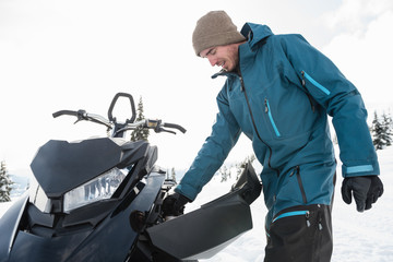 Man repairing snowmobile in snowy alps