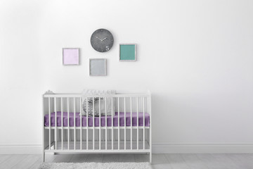 Baby room interior with crib near wall