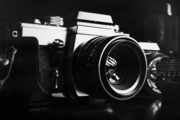 Black and white image of vintage film cameras and lenses