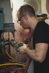 Glassblower working on a glass piece
