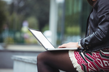 Mid section of woman using laptop