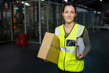 Portrait of young female worker standing in warehouse