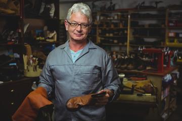 Portrait of man standing in workshop
