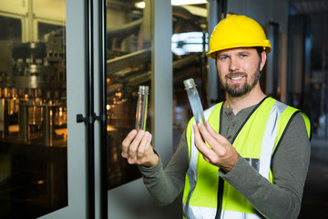 Male worker examining juice in test tube at factory