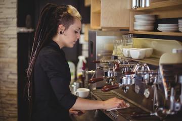 Waitress wiping espresso machine with napkin
