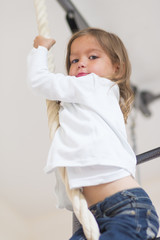 Children Concepts. Portrait of Caucasian Girl Having Physical Exercises on Rope of Wall Bars Indoors.