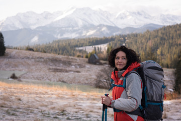 Thoughtful woman standing with backpack and hiking pole