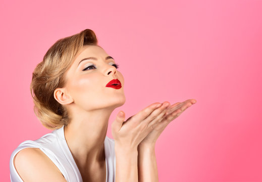 Skincare, haircare, beauty concept - woman with perfect skin, red lips blowing kiss from hand. Beautiful girl showing empty copy space on open hand palm for text. Copy space for advertise beauty salon