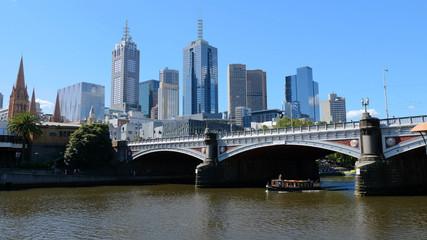 Melbourne, Australia. Skyscrapers and the bridge over the Yarra river. Boat passes through the Princes Bridge
