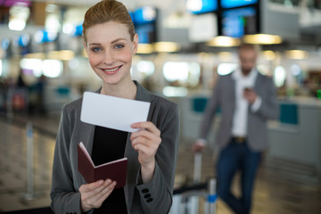 Portrait of smiling businesswoman showing her boarding pass