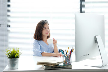 Young asian woman holding a coffee cup with smiling face, positive emotion at working desk background, casual office life, worink at home concept