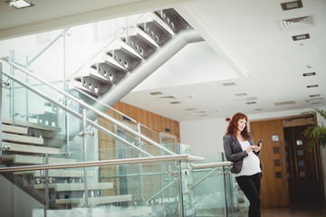 Pregnant businesswoman using mobile phone near staircase