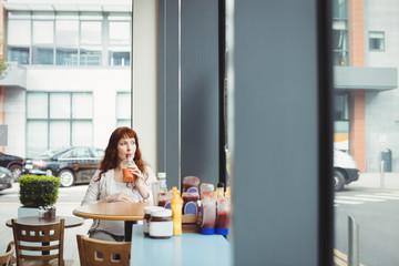 Pregnant businesswoman having fruit juice in cafeteria