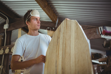 Young man working on surfboard in workshop
