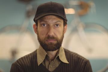 Portrait of owner wearing cap at workshop