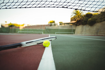 Tennis racket and ball lying in the court