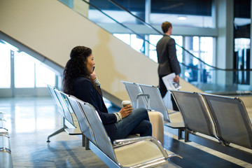 Female commuter with coffee cup talking on mobile phone in waiting area