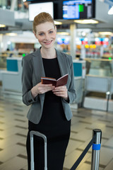 Smiling businesswoman with luggage checking her boarding pass