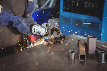 Welder cutting metal with electric tool in workshop
