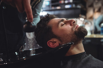 Man relaxing while getting his hair wash