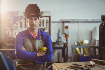 Portrait of male welder standing with arms crossed