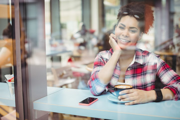 Smiling young woman seen through restaurant window