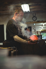 Glassblower shaping a blown glass piece with a wet cloth