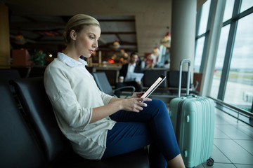 Female commuter using digital tablet in the waiting area