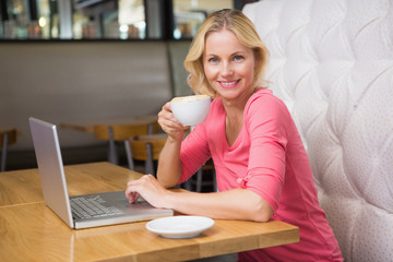 Woman having a coffee using laptop