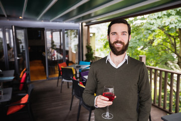 Man holding glass of wine in bar